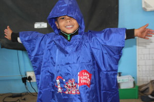 Closeup of little boy arms open wide in poncho